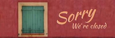 muro coloe ruggine, con porta verde chiusa, scritta Sorry, we are closed
